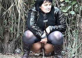 Молодая женщина писает на полянке